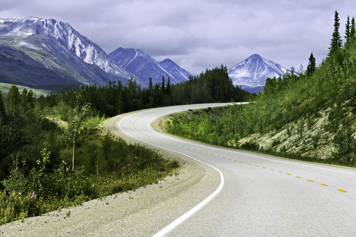 curved asphalt road in high mountains, Alaska